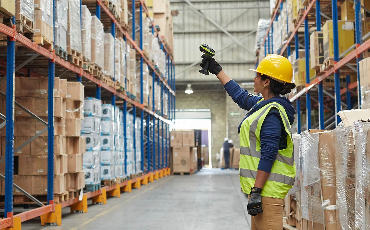 Warehouse worker scanning product on high shelf