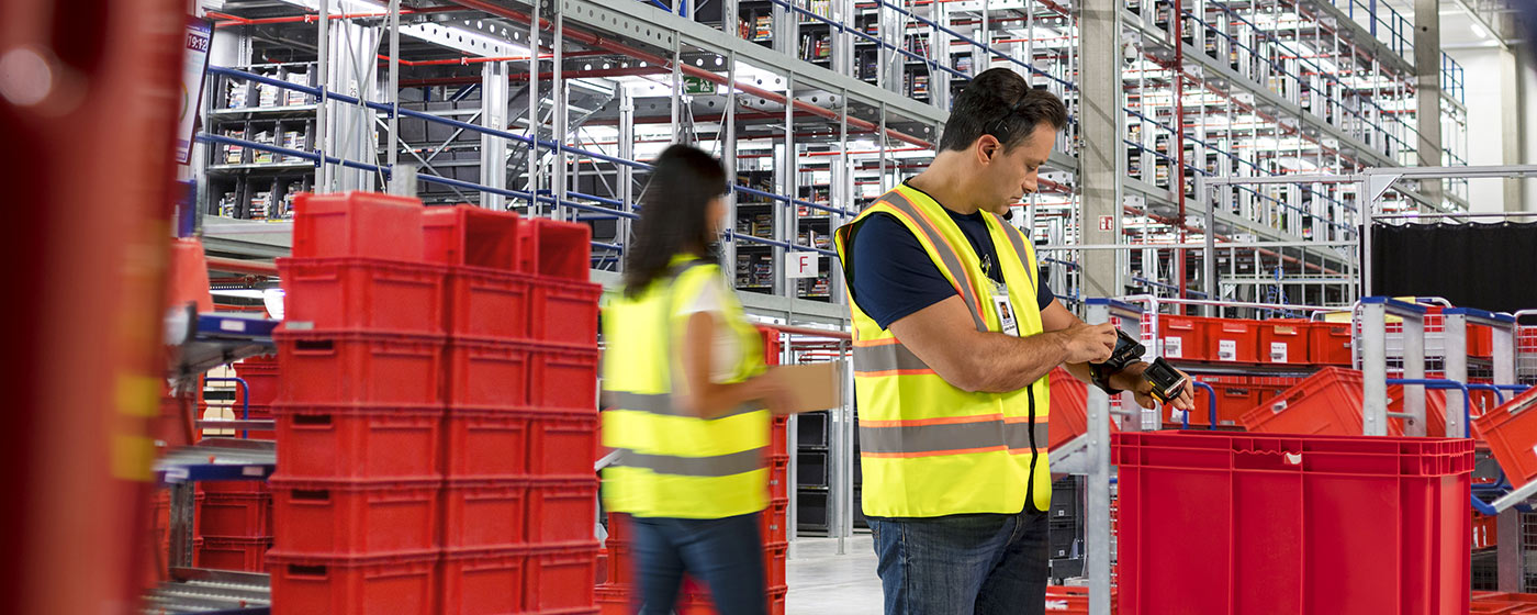 A couple workers in distribution center - one is using ring scanner and wearable