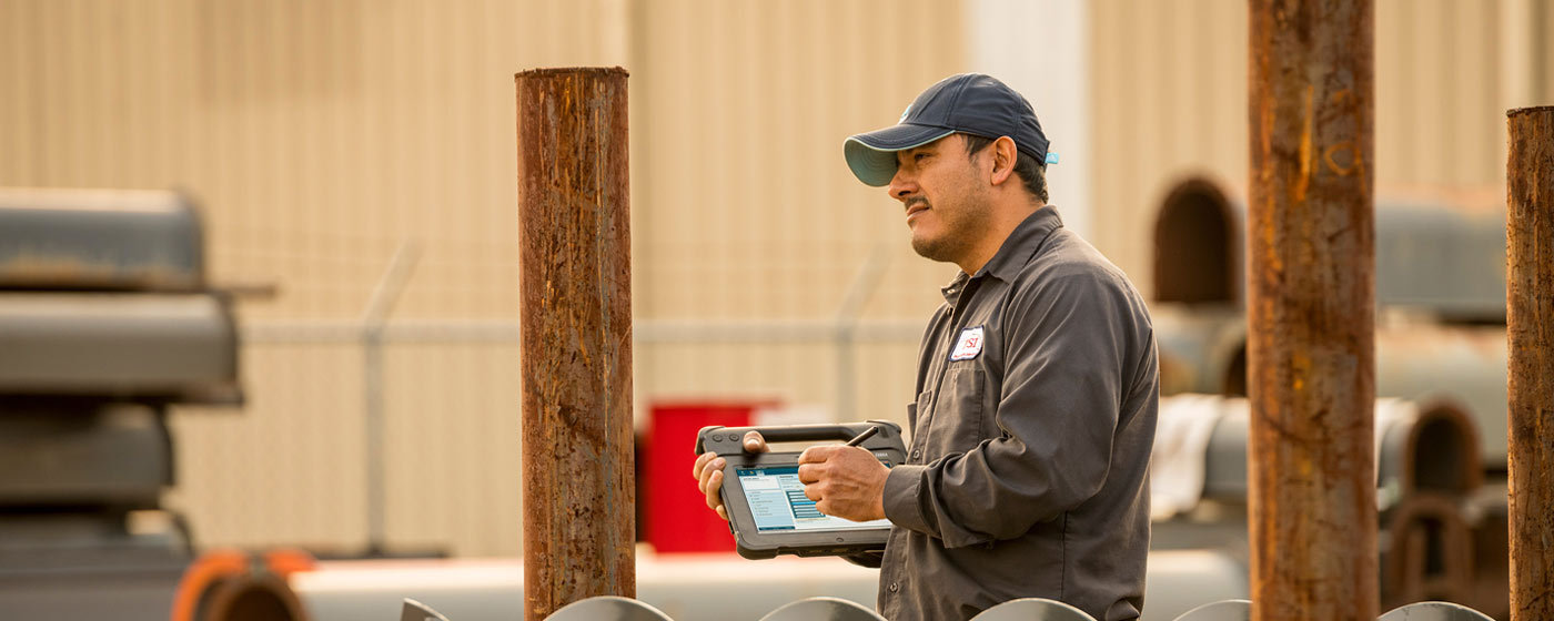 Worker outside warehouse using rugged tablet