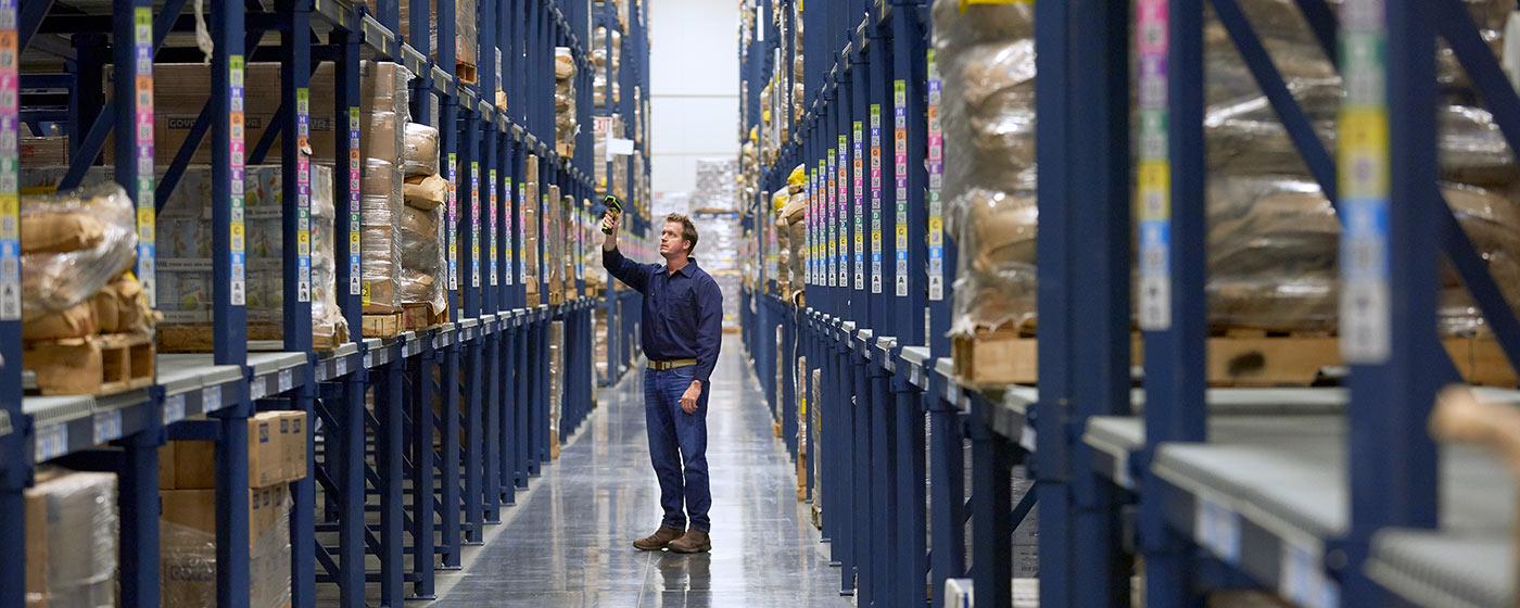 Warehouse worker scanning item on high shelf