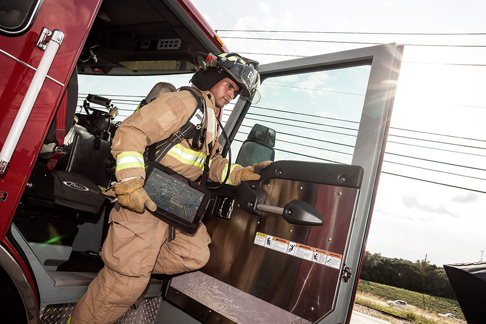 Firefighter exiting fire truck and carrying XSLATE R12 tablet